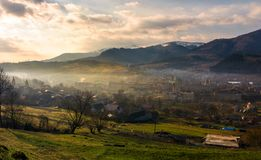 Cloudy and foggy sunrise in Carpathian mountains. Small town Volovets in the valley at the foot of Borzhava mountain ridge with snowy tops. lovely springtime Stock Photography
