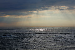 Cloudy glistening seascape with sunbeams Royalty Free Stock Images