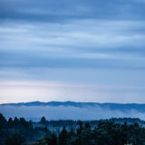 Cloudy hilly landscpe. Foggy hilly ground in front of a mountain chain with trees in the foreground Royalty Free Stock Photos