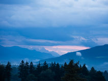 Cloudy hilly landscpe. Sunset in the mountains with rows of green trees in the foreground Royalty Free Stock Photo