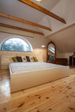 Cloudy home - huge bed. Cloudy home - huge bright bed in wooden bedroom interior royalty free stock photo