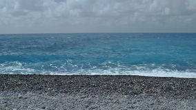 Cloudy Horizon beyond Pebble Stone Beach. Static low angle medium long high dynamic range shallow depth of field shot of foamy sea waves rolling on a pebble stock video footage