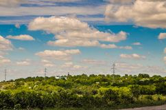 Cloudy landscape. Electric wires above the trees Royalty Free Stock Photography