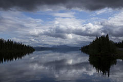Cloudy landscape. Lake on a very cloudy day wit dark forest and mountain in the background Stock Images