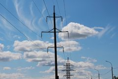 Cloudy landscape with a power line / Bright sunny day /. Electric steel structures Royalty Free Stock Photography