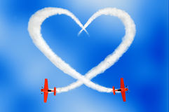Cloudy love is in the air concept. Two air-planes drawing a cloudy love is in the air concept in the sky with smoke Royalty Free Stock Photos