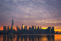 Cloudy Manhattan Sunrise. Colorful clouds over Manhattan at sunrise from Jersey City Royalty Free Stock Image