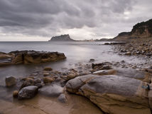 Cloudy Mediterranean Rocky Beach. Cloudy seascape on a rocky beach with a mountain on the foreground Royalty Free Stock Images