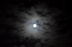 Cloudy moon. Moon showing on through the stormy clouds Royalty Free Stock Photography