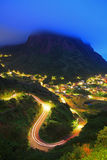 Cloudy mountain and light trail on a curve at evening Stock Photos
