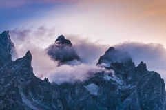 Cloudy mountain peaks at sunset Stock Images