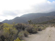 Cloudy Mountains in California Desert. The clouds roll over the mountains like mist somewhere in Panamint Valley, California Stock Photo