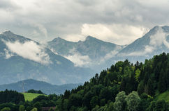 Cloudy Mountains. Landscape from allgaeumeaddows and woods to some alp mountains stock image