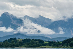 Cloudy Mountains. Landscape from lake forggen over allgäumeaddows and woods to some alp mountains Stock Image
