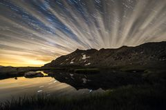 Cloudy Night on a mountains. Long exposure of a cloudy night reflected on a Lagoon of the Birds in the mountain of Peñalara,Spain royalty free stock photos