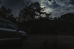 A cloudy night sky with moon light in the mysterious forest. Parked car royalty free stock images
