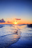 Cloudy orange sunset over sea water, sunset over sea waves. Stock Image