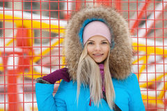 Cloudy outdoor winter portrait of young happy adorable woman in bright cyan coat posing in winter city park against bright red and Stock Image