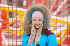 Cloudy outdoor winter portrait of young happy adorable woman in bright cyan coat posing in winter city park against bright red and Royalty Free Stock Images