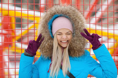 Cloudy outdoor winter portrait of young happy adorable woman in bright cyan coat posing in winter city park against bright red and Royalty Free Stock Photos
