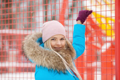 Cloudy outdoor winter portrait of young happy adorable woman in bright cyan coat posing in winter city park against bright red and Royalty Free Stock Photo