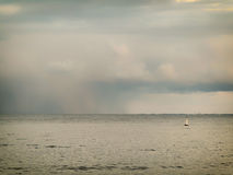 Cloudy overcast sky above a surface of the sea Stock Images