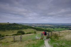 Cloudy overcast summer sunrise over the South Downs Way footpath from A middle aged male walker with backpack admiring the view stock image