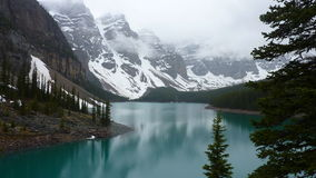 Cloudy peaks above Moraine Lake, Canada. The dark turquoise waters of Moraine Lake in Banff National Park, Alberta, Canada with wisps of clouds just starting to Stock Photos