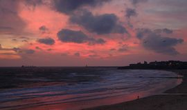 Cloudy, pink sunrise on Tynemouth Longsands beach royalty free stock photography