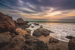 Cloudy Point Dume Sunset. Dramatic sky at sunset along Point Dume State Beach with waves crashing into rock formations along the beach, Malibu, California Stock Photo