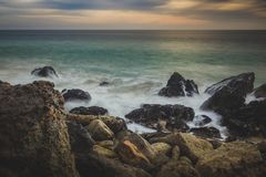 Cloudy Point Dume Sunset. Dramatic sky at sunset along Point Dume State Beach with waves crashing into rock formations along the beach, Malibu, California Stock Image
