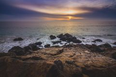Cloudy Point Dume Sunset. Dramatic sky at sunset along Point Dume State Beach with waves crashing into rock formations along the beach, Malibu, California Royalty Free Stock Image