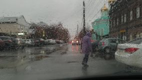 Cloudy and rainy autumn day, view of the city from the car window, a pedestrian crosses the road stock video