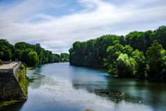 Cher river  with smooth reflection under blue sky running through green forest. Cloudy rainy sky ,green Cher river & forest view outside the windows in Loire Royalty Free Stock Photos