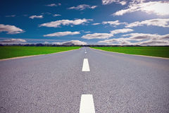 Cloudy road. Asphalt road in field on cloudy day Royalty Free Stock Photography