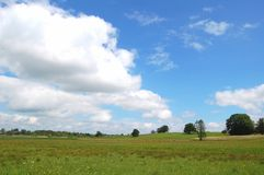 Cloudy Scenery with blue sky, Bavaria, Germany. White clouds dominating the image are on the left, blue sky is on the right. In front is a meadow. Some trees are Stock Images