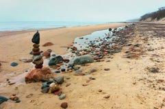 Cloudy sea shore, pyramid of sea stones. Pyramid of sea stones, cloudy sea shore royalty free stock photos