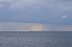 Cloudy seascape with sailing yacht and floating lighthouse Stock Image
