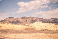 Cloudy skies hang over the desert of Death Valley. With a mountain range in the distance royalty free stock image