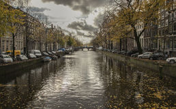 Cloudy skies over a canal, Amsterdam. A view of a canal and in Amsterdam, the Netherlands. It was taken on a cloudy day in autumn Royalty Free Stock Image