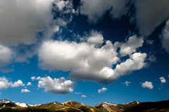 Cloudy skies over mountains. Cloudy deep blue skies over mountain tops Stock Images