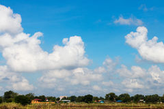 Cloudy skies over the village. Background cloud sky scenery rural village, which is covered with forest with grass foreground Royalty Free Stock Photos