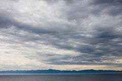 Cloudy skies over water. Cloudy skies over the ocean with mountains in the background Stock Photo