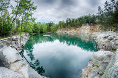 Cloudy skies and reflections at a quarry Stock Image