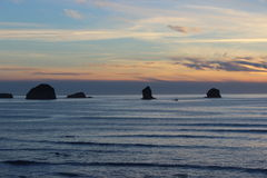 Cloudy skies and sunset over Oregon Coast Pacific ocean rocky outcrops. Cloudy skies and orange sunset hues over the Oregon West Coast Pacific Ocean and rocky Royalty Free Stock Images