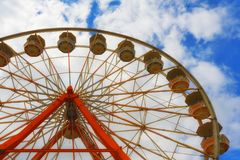Cloudy skies and the top of a ferris wheel Stock Photos
