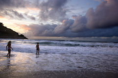 Cloudy sky. Two kids playing on the beach without surveillance at the sunset.  The sky is very nebulous Stock Image