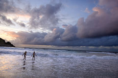 Cloudy sky. Two kids playing on the beach without surveillance at the sunset.  The sky is very nebulous Stock Photos