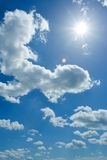 Cloudy sky. Cumulus clouds and the sparkling sun on the blue summer sky stock image
