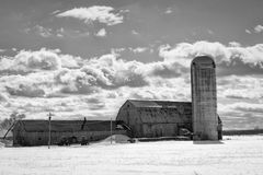 Cloudy sky above barn and silo Stock Images